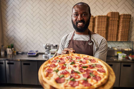 Cheerful male pizzaiolo in apron looking at camera and smiling while holding delicious pepperoni pizza