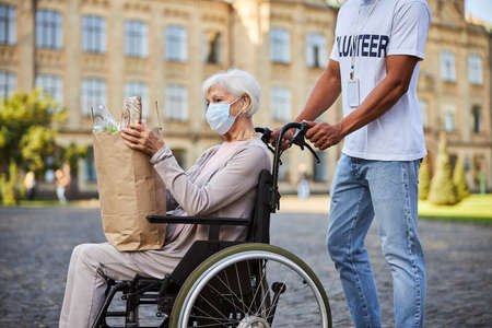 Elderly lady sitting in a wheelchair with a shopping bag full of food. Unrecognized volunteer pushing the handles