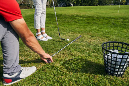 Cropped photo of a trainer placing his club on the teeing ground along the tips of his client toes Stock fotó