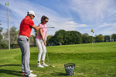 Concentrated dark-haired young woman in sunglasses getting into a golf stance assisted by her tutor Stock fotó