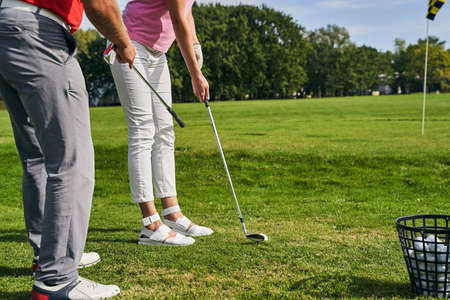 Cropped photo of an instructor teaching a beginner golfer to get into a proper golf stance Stock fotó