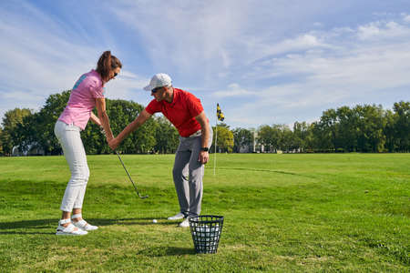 Experienced male instructor teaching a young woman to hold a club correctly during the game