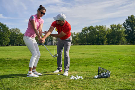 Serious beginner golfer in sunglasses learning to hold a club assisted by her personal coach