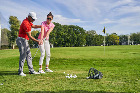 Young female athlete practicing a golf swing on the course helped by a skilled instructor