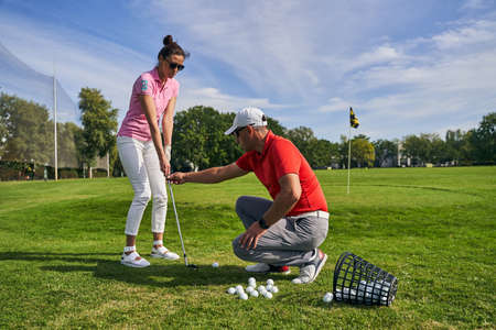 Focused dark-haired beginner lady golfer practicing a proper grip technique assisted by her male instructor