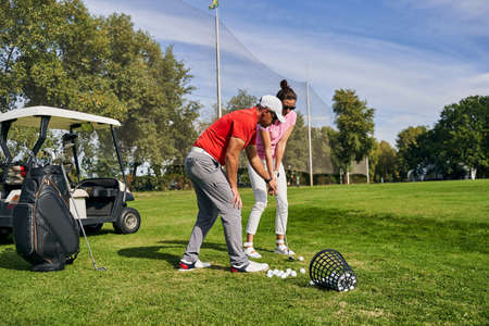 Young dark-haired woman in sunglasses learning to use a golf club assisted by her personal trainer
