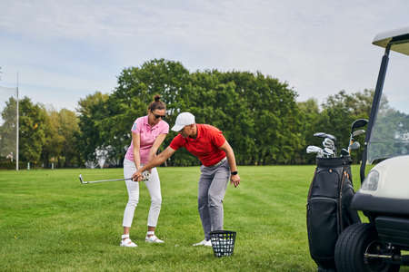 Cheerful female beginner learning to hit the ball with a mid-iron assisted by her trainer Stock fotó