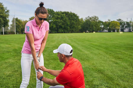 Concentrated beginner golfer learning how to grip a golf club helped by an experienced tutor