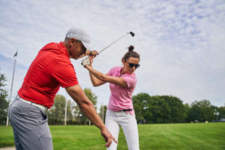 Focused young woman golfer holding a mid-iron over her head helped by her personal trainer Stock fotó