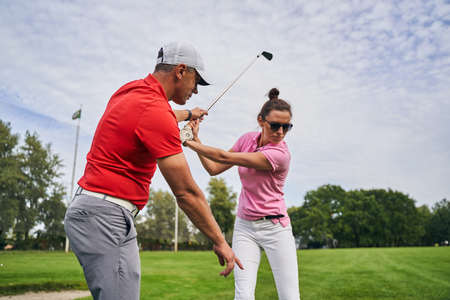 Skilled middle-aged male instructor in a cap explaining the golf fundamentals to a female beginner Stock fotó