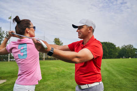 Smiling middle-aged male instructor in a cap teaching a woman in sunglasses the golf basics Stock fotó