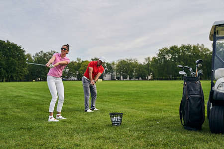 Smiling young woman and her male instructor swinging their golf clubs with slightly bent knees Stock fotó