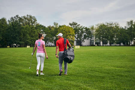 Back view of a female athlete in sunglasses and her personal trainer crossing the golf course