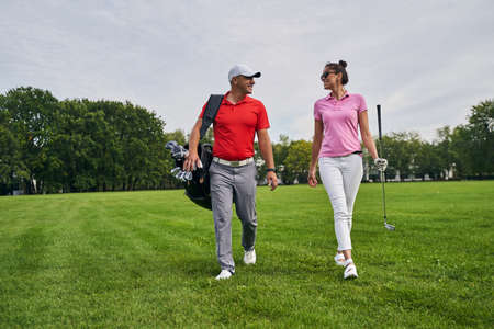 Front view of a smiling lady with a golf club walking next to a professional coach Stock fotó