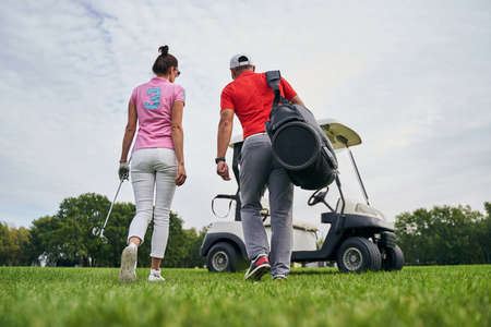 Back view of a female golfer and her male instructor going toward a golf car Stock fotó