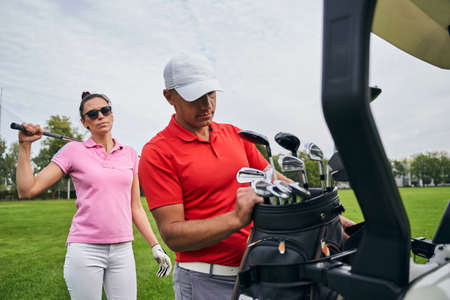Slim dark-haired Caucasian female golfer in sunglasses standing behind her personal trainer in a cap