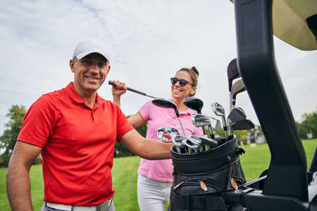 Joyous dark-haired Caucasian female athlete and a professional male trainer standing by a golf car Stock fotó