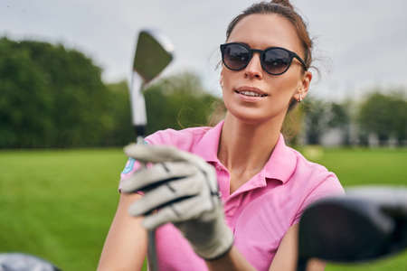 Portrait of a young focused female player staring at the wedge club in her hand Stock Photo