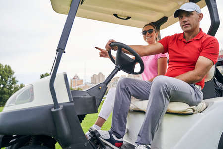 Focused middle-aged Caucasian man in a cap driving a female passenger in a golf car
