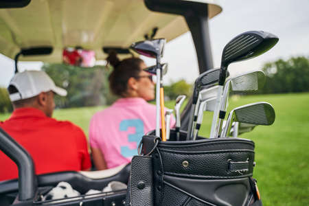 Back view of a man in a cap and a dark-haired woman riding in a golf car