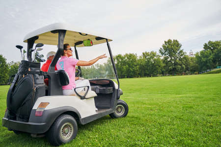 Smiling lady in sunglasses pointing at something to a golf car driver in a cap