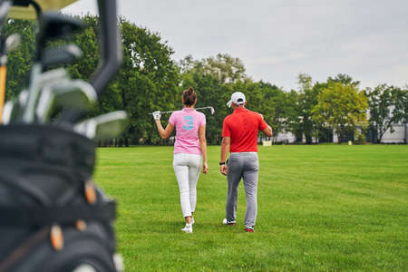 Back view of a dark-haired slim woman and a man in a cap crossing the golf course Stock fotó