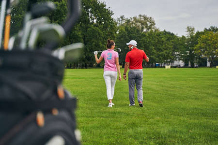 Back view of a female golfer and her personal coach in a cap crossing the driving range Stock fotó