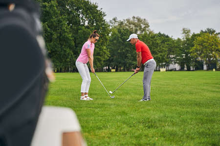 Side view of two Caucasian golfers with clubs standing against each other on the lawn