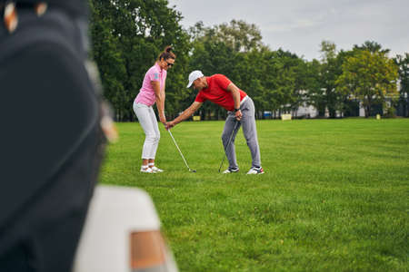 Side view of a smiling woman practicing the proper golf grip assisted by her trainer
