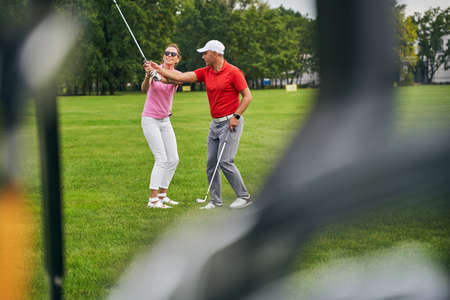 Front view of a pleased woman learning how to hold her club helped by her trainer