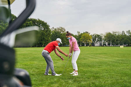Side view of a professional trainer leaning towards a club in the female player hands