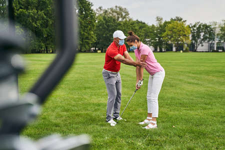 Focused woman golfer learning to get into a proper stance assisted by her personal coach