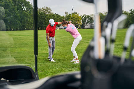 Concentrated beginner golfer attempting to hit the ball with an iron club helped by her trainer Stock fotó