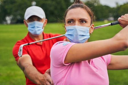 Female beginner golfer in a face mask mastering the downswing technique supported by her coach Stock fotó