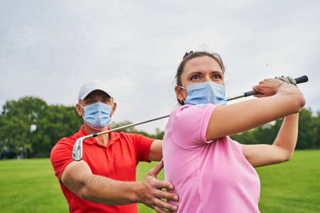 Professional male instructor in a disposable face mask guiding a beginner golfer during the training