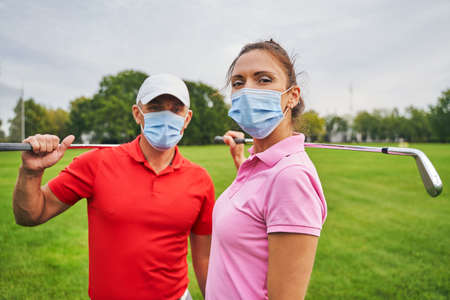 Two modern golfers in disposable face masks and polo shirts standing on the golf course Stock fotó