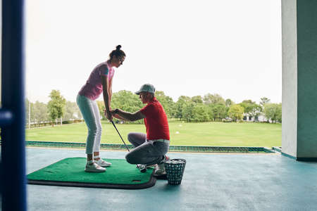 Side view of a golfer learning to grip the iron club helped by her coach Stock fotó