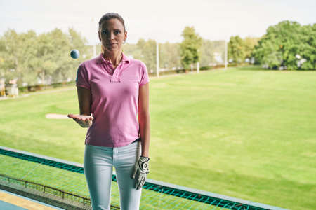 Front view of an attractive calm sporty young dark-haired Caucasian sportswoman juggling a golf ball