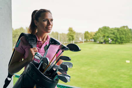 Front view of a beautiful lady golfer with a dreamy smile staring into the distance Stock Photo