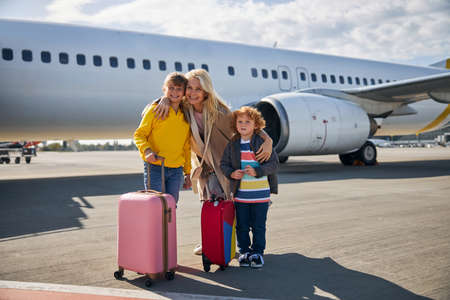 Joyful female parent hugging her two children by the shoulders on a runway while standing beside a plane with suitcases 写真素材