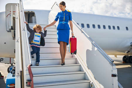 Cabin attendant wearing a blue outfit helping a small boy with an identity form in getting off the plane