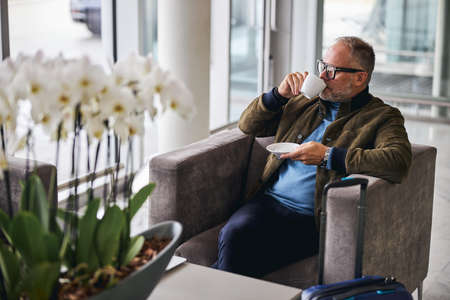 Adult Caucasian male traveler in eyeglasses with a cup of beverage sitting by the window