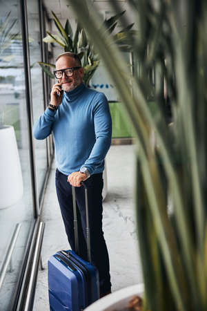 Smiling pleased businessman leaning one hand on the retractable suitcase handle during the phone conversation 免版税图像