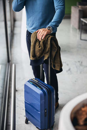 Cropped photo of a man in casual clothes leaning on the hand on the suitcase handle