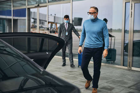 Caucasian man in a disposable protective mask and eyeglasses walking toward the parked elite taxi