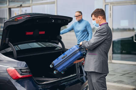 Serious elegant dark-haired Caucasian airport driver putting his client traveling bag in the car trunk