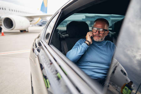 Waist-up portrait of a smiling businessman in eyeglasses talking on the cellphone in the car