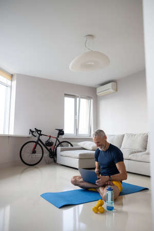 Athletic middle-aged person having fun with a laptop while practicing yoga on a mat in a spacious white room