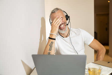 Entrepreneur roaring with laughter and covering his eyes with right hand while communicating with headset through laptop