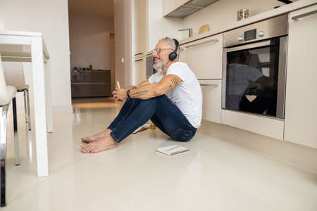 Inspired businessman locking his hands with a phone in front of him while taking a seat near a cooker